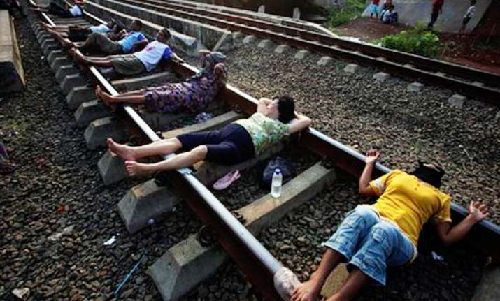 indonesians lie on rail tracks for electric therapy