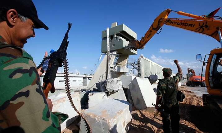 libyans tearing down gadhafi s tripoli compound