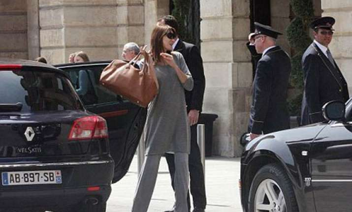 pregnant carla bruni tries to hide her bulging belly