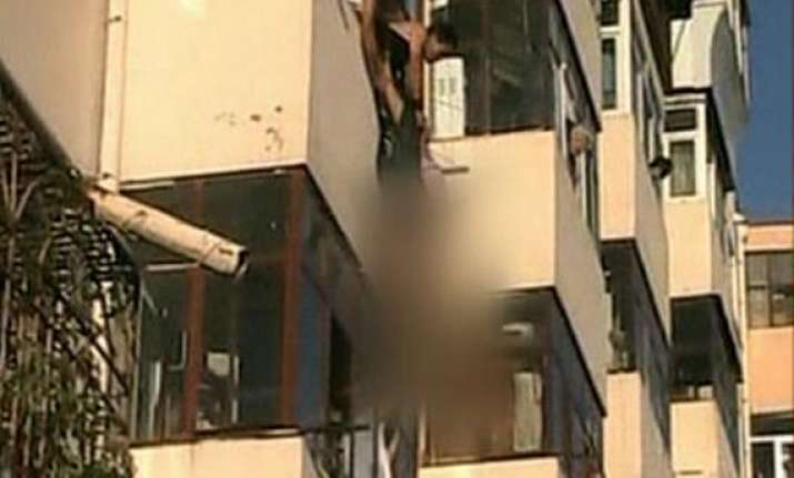 woman pulled to safety after dangling from fourth storey