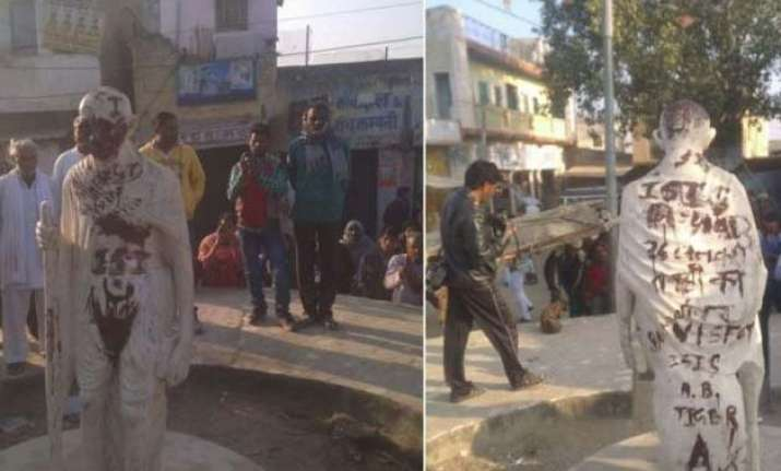 mahatma gandhi statue defaced with pro isis slogans in