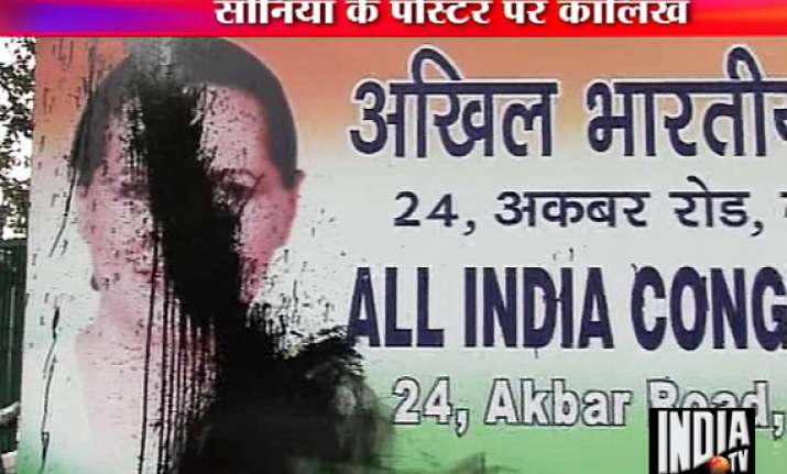 man throws black paint on sonia gandhi s poster outside