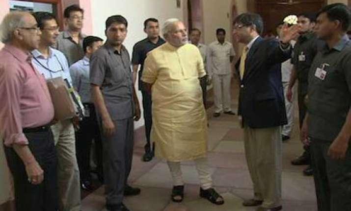 narendra modi walks through pmo posts picture
