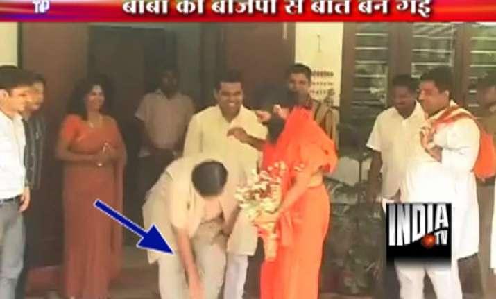gadkari touches ramdev s feet seeks his blessings