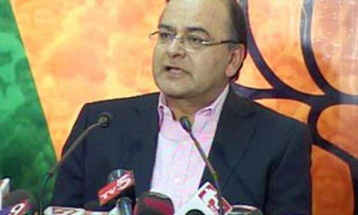 bjp criticises pm for defending raja in spectrum scam