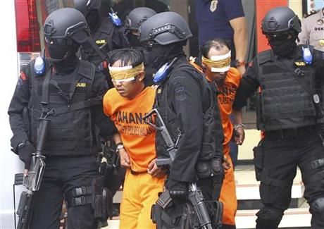 Indonesian police officers escort suspected millitants