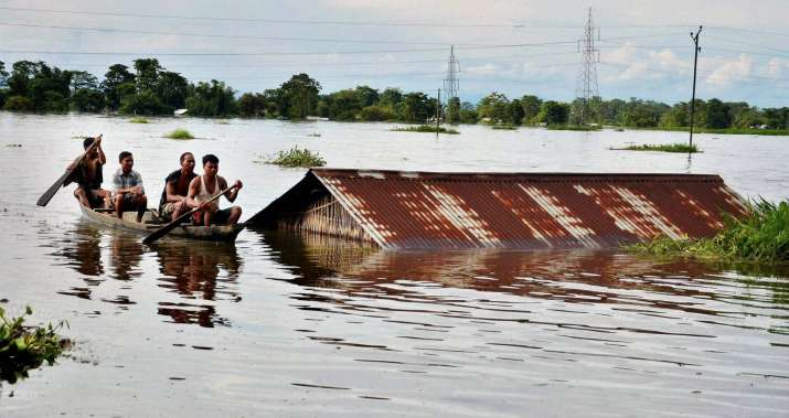 India Tv - Villagers move on a boat past submerged houses near a village in Kaziranga
