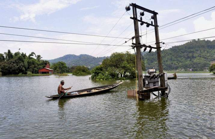 A villager uses a boat to cross flood water in Rajabari