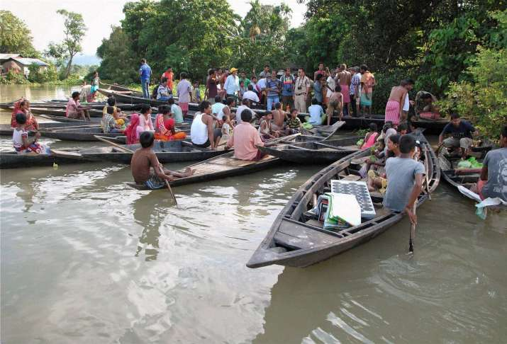 India Tv - Villagers gather to collect relief material at Dhipujijan Pam in West Mayong