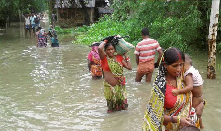 India Tv - Katihar Villagers cross a flooded road in Katihar district of Bihar on Saturda