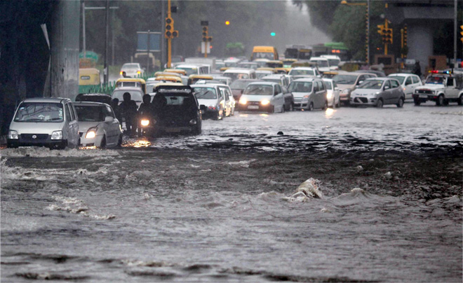 Vehicles make way through waterlogged road in Delhi on