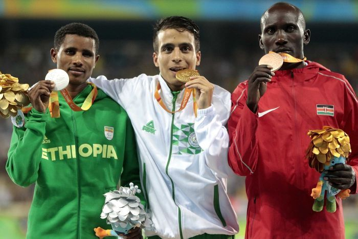 Abdellatif Baka centre shows off his gold medal alongside
