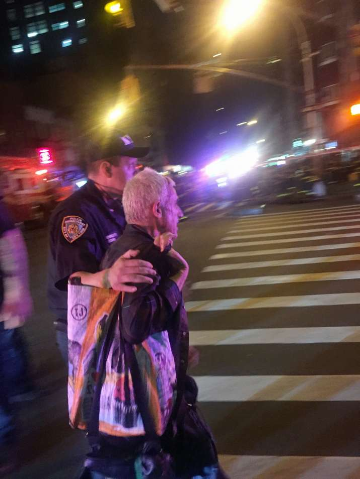 India Tv - Police officer escorts an injured man away from scene of explosion in New York