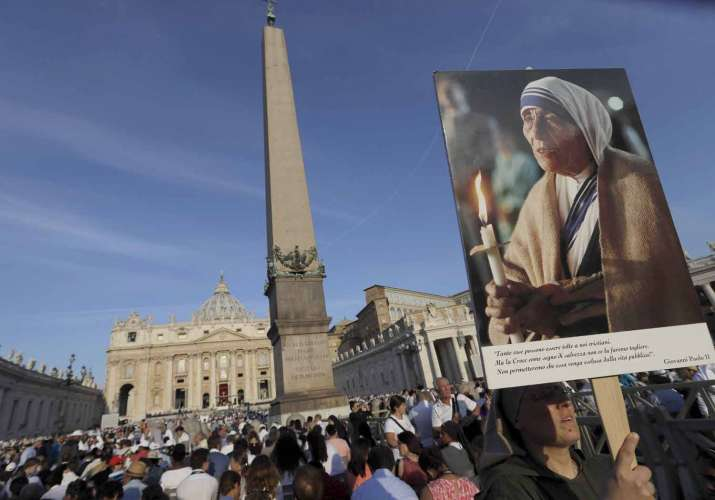 A nun holds a photo of Mother Teresa before the start of