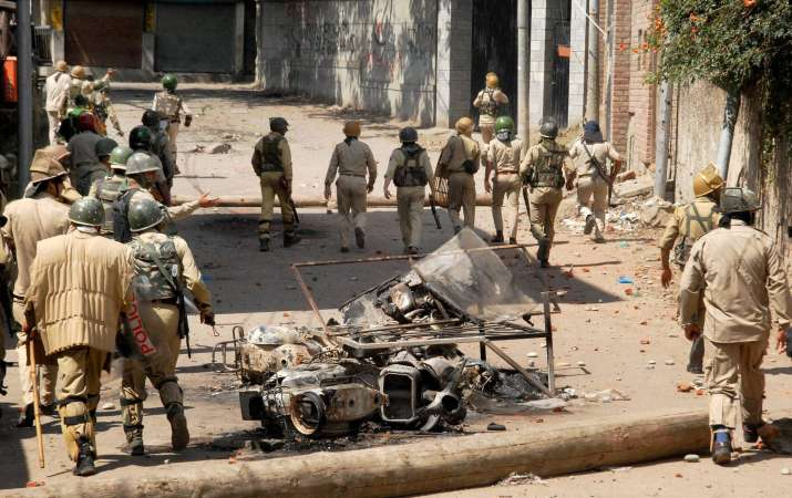 Security personnel chasing away stone throwing youth in