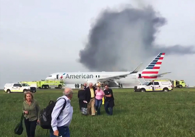 Passengers walk away from a burning American Airlines jet