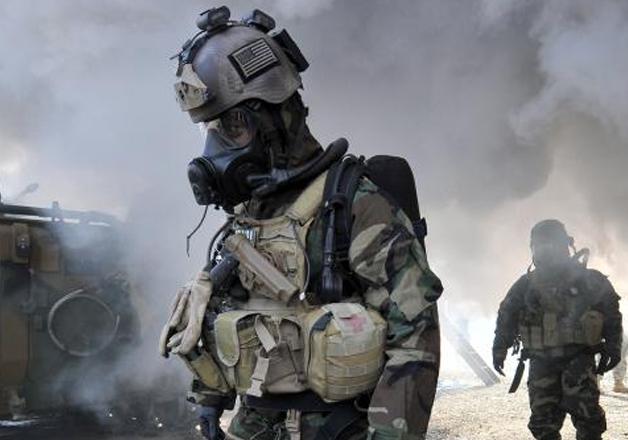 US soldiers wearing chemical warfare gear walk through