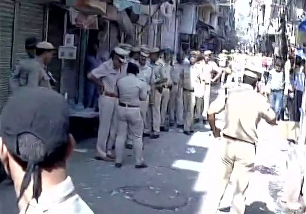Delhi Police personnel arrive in Naya Bazar where an