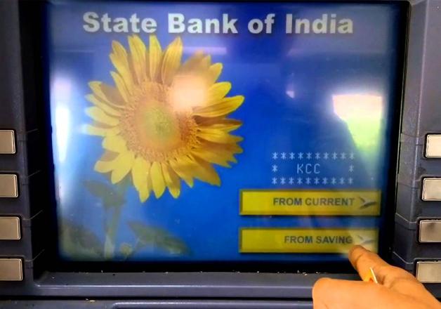 File pic - A man operates SBI ATM machine