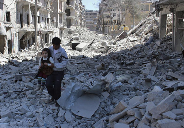 A Syrian man holding a girl as he stands on the rubble of