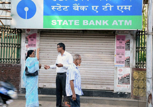 People stand as an ATM closed for the day due to