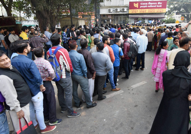 People stand in queue out a bank in New Delhi