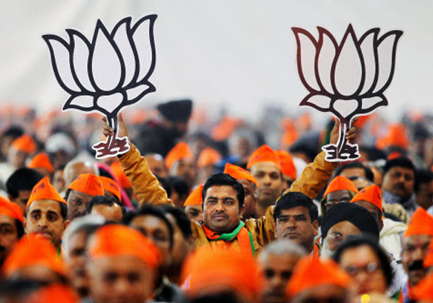File pic - A BJP worker displays party's symbols at a rally.
