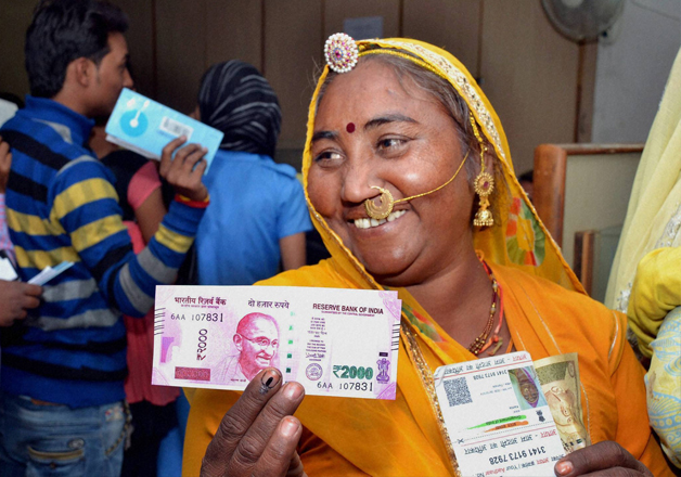 A rural woman senior citizen after exchanging Rs 500 and