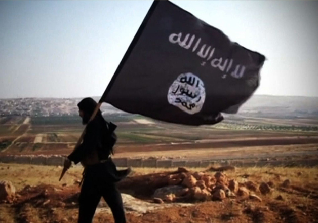 File pic - ISIS militant waves terror outfit's flag