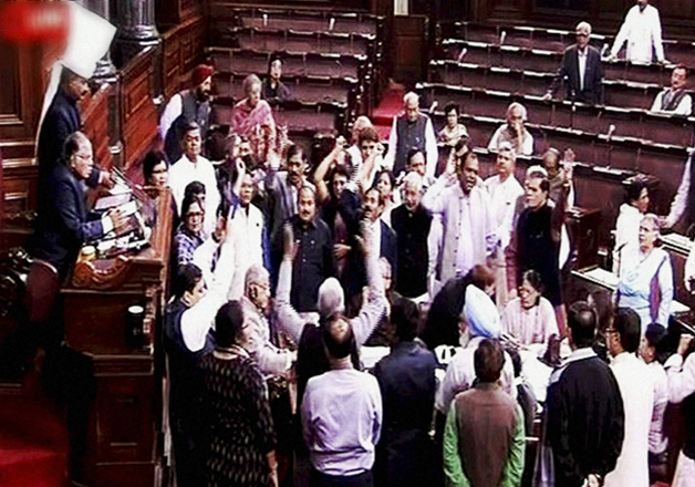 Opposition members protest in the well of the Rajya Sabha