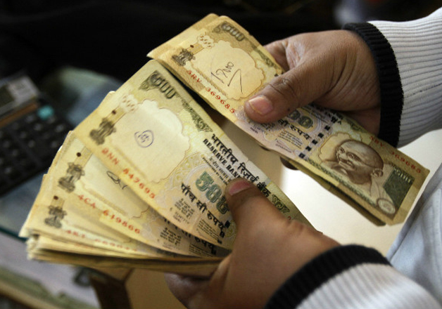 File pic - A man counts now scrapped Rs 500 notes