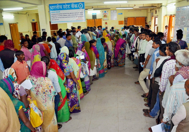 People stand in queue at a SBI branch to exchange their