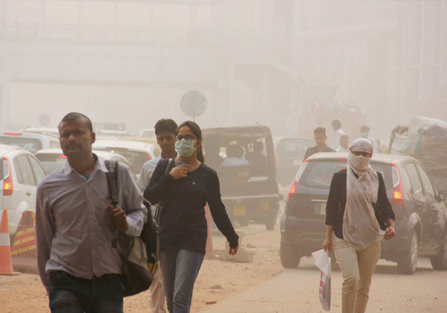 People take protection against pollution as they commute