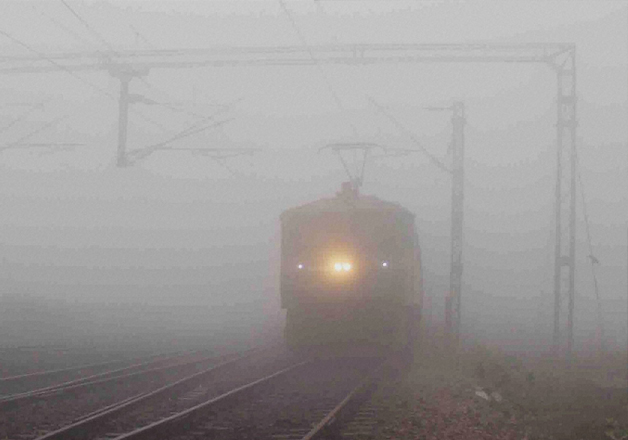 A train moves slowly amid a thick blanket of fog on a cold