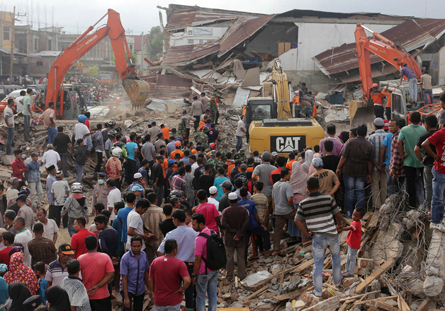 Rescuers search for victims under the rubble of collapsed