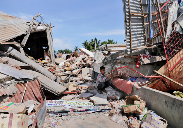 India Tv - A boy sits on the rubble of a building that collapsed after an earthquake
