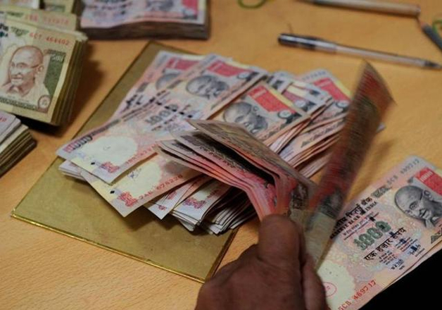 File pic - A bank official counts scrapped Rs 1000 notes