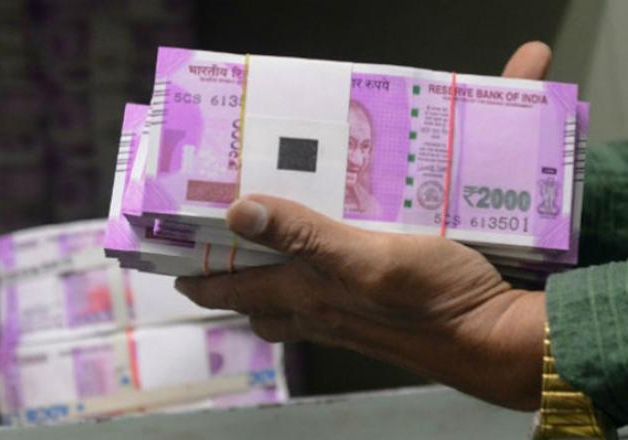 File pic - A bank official carrying new Rs 2,000 notes