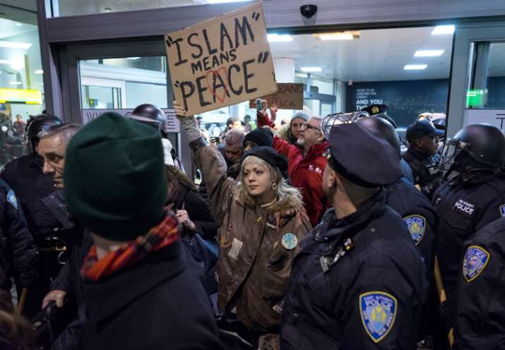 India Tv - Protesters surrounded by police officers and travelers at JFK Airport, New York