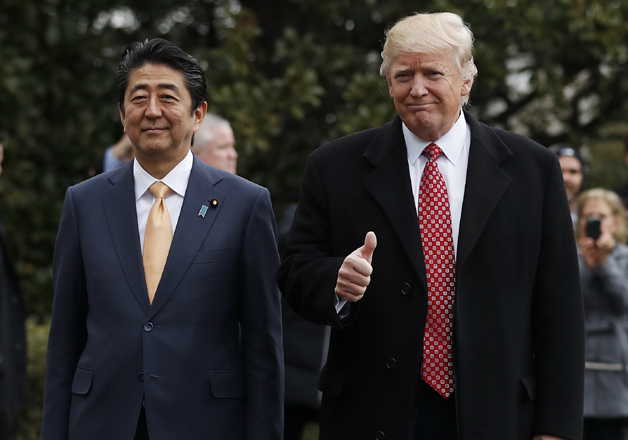 Donald Trump and Shinzo Abe pause before boarding Marine One