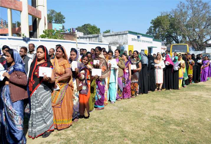 Women voters wait to cast their votes at a polling station