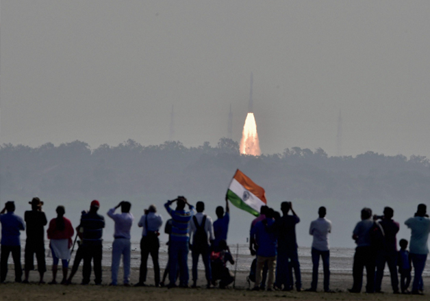 People watch as an ISRO rocket takes off successfully to