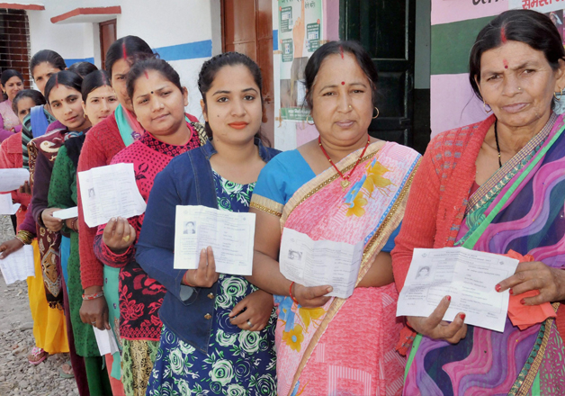 Women stand in line to cast their vote during Uttarakhand