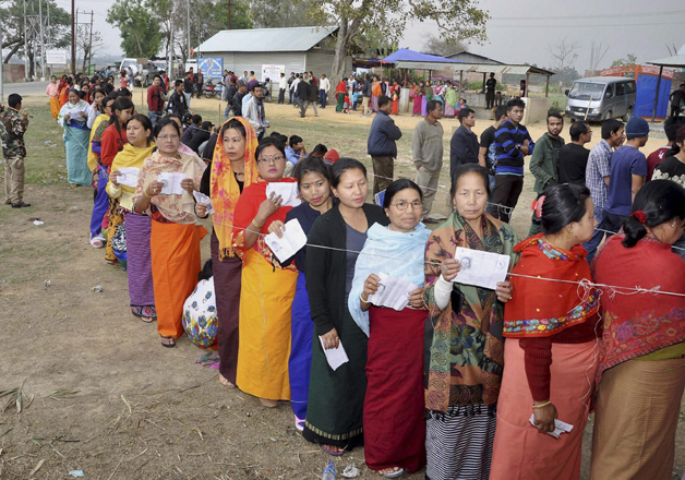 Voters stand in queues at a polling center to cast their
