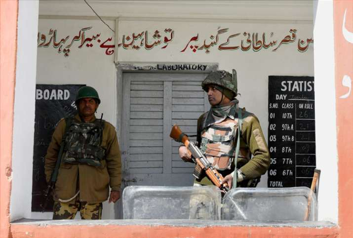 A jawan stand guard outside a polling station for Srinagar