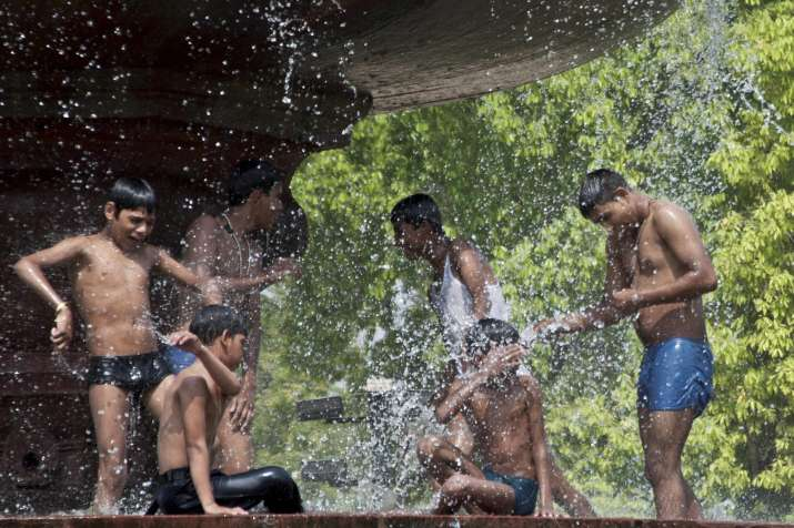 Youngsters splash water at a fountain near India Gate to
