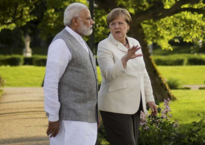 Angela Merkel and Narendra Modi walk through the garden of