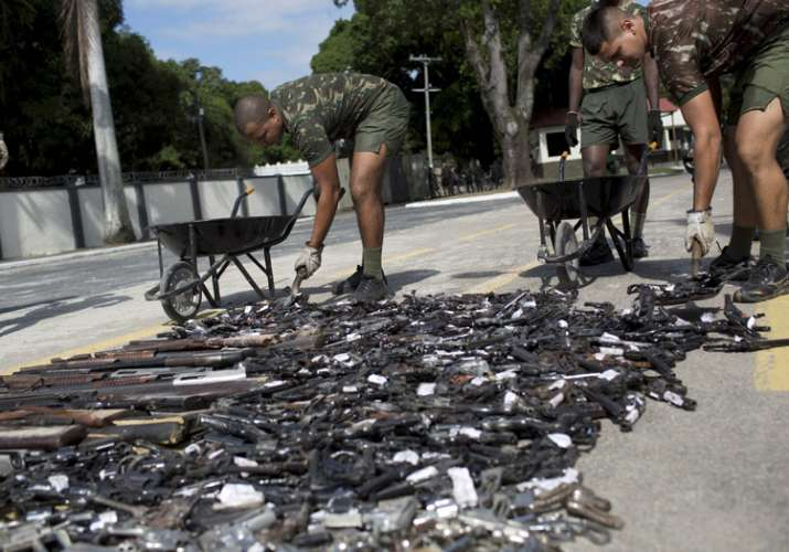 India Tv - Military personnel pick up trashed weapons