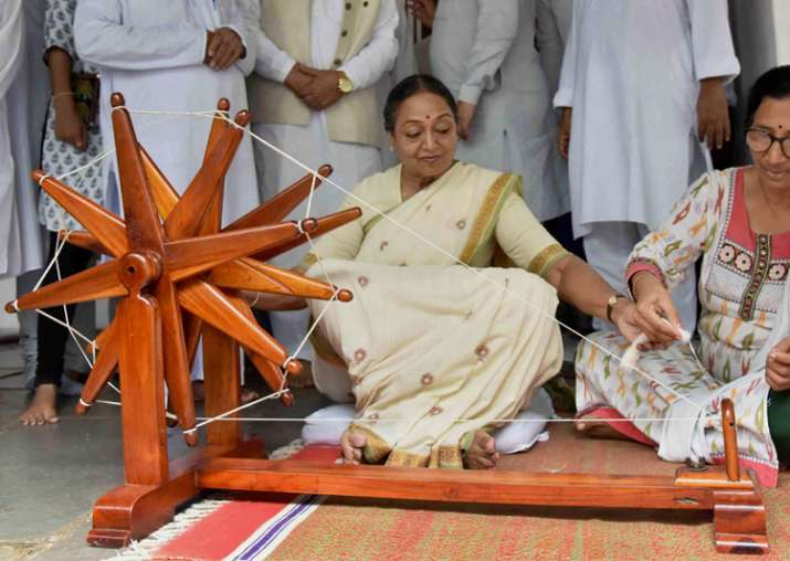 Meira Kumar tries her hand on a spinning wheel during her