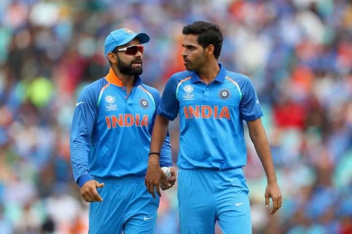 Virat Kohli and Bhuvneshwar Kumar of India chat in the field